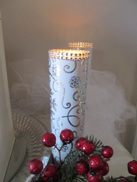 An inexpensive candle that has been decorated with wrapping paper and gems.