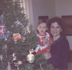 A mother and son next to a Christmas tree.