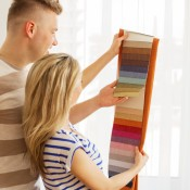Man and a woman looking at curtain fabric swatches.