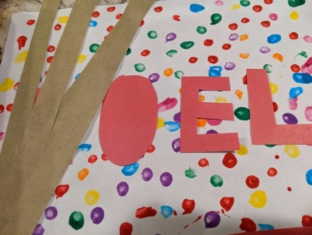 Noel Q-Tip Painting - brown paper border and red paper letters cut out