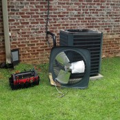 air conditioner unit outside home with tool kit next to it