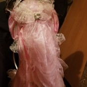 Value of a Knightsbridge Collection Porcelain Doll - doll wearing a pink dress and matching hat, both trimmed with white lace
