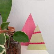 Minimal Cardboard Christmas Tree Decoration - two trees next to a plant on the mantle