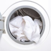 An open dryer with a white towel.