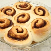 A glass pie plate filled with cinnamon rolls.