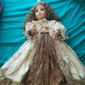 Value of an Ashton Drake Porcelain Doll - doll wearing a long dress with taupe lace