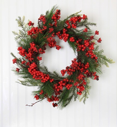 A wreath made from greenery and red berries.