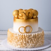 Two tiered cake with wedding rings and a 50 on top.