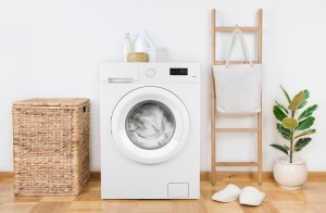 Washing machine in laundry room with natural decor.