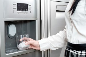 Woman getting ice from fridge.
