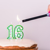 Lighting candles on a 16th birthday cake.