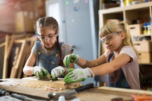 Two young girls working on a craft project with wood.