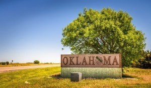 "A road sign that states ""Oklahoma"" next to a tree and sky vista."