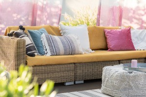 Colorful curtains behind a rattan couch with many pillows.