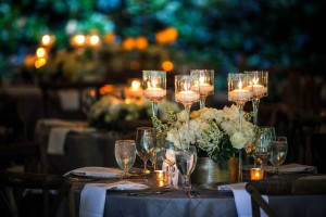 Wedding table with candles in tall glass cups.