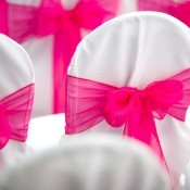 Wedding Chair Covers in white with pink bows.