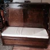 Value of a Foldout Bed - fold out bed with tall wooden headboard with carved decorations on headboard and arms