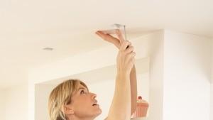 A woman fixing a light fixture.