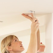 A woman fixing a light fixture.