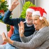 A couple waving at a tablet screen at Christmastime.