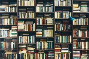 Books stored horizontally and vertically on shelves.