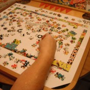 A game board being used to assemble a puzzle.