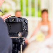 A photographer taking a picture of a wedding couple.