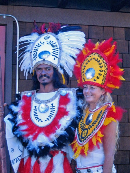 A couple dressed in Tahitian costumes for a wedding anniversary celebration.