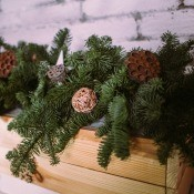 Branches trimmed off a Christmas tree are used to decorate a fireplace mantle or shelf.