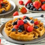 A plate of Belgian waffles served with fruit.