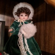 Identifying a Porcelain Doll - doll wearing a dark green velvet coat and hat with white trim and matching muff