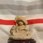 Identifying a Giuseppe Armani Figurine - figurine mounted on round brown base, child sitting in front of a picket fence