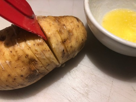 adding butter to slits in Potato