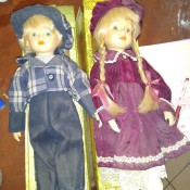 Identifying Porcelain Dolls - boy doll in jeans and plaid shirt and girl with braids and a lace trimmed dress with pantaloons.