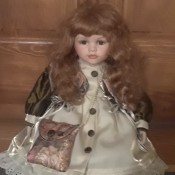 Identifying a Porcelain Doll  - sitting doll wearing a brown and cream satin coat carrying a brocade shoulder bag