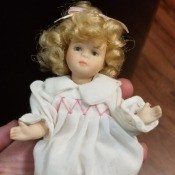 Identifying a Porcelain Doll - small blonde doll wearing a long white nightgown with pink smocking