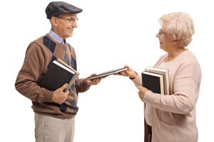 Two older people exchanging books.