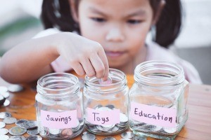 A child placing coins into three jars, marked savings, toys and education.