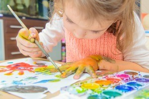 A girl painting her fingers and paper with watercolors.