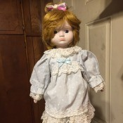 Value of a Heritage Porcelain Doll - red haired doll wearing a lace trimmed light blue dress and pantaloons