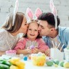 A man, woman and child with bunny ears on, decorating eggs.