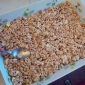 pressing Cheerio Peanut Butter treats into pan