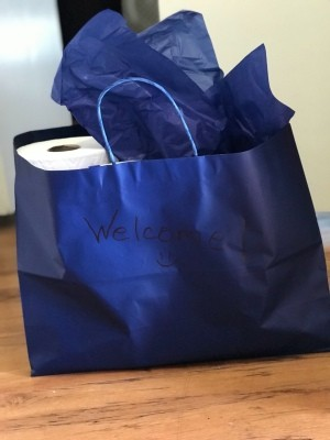 A gift bag filled with cleaning supplies as a welcome gift.