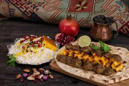 A selection of Persian (Iranian) foods next to a traditional rug.