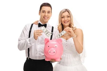 Bride and groom adding money into a piggy bank.