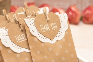 Wedding favors in brown paper bags embellished with paper doilies.