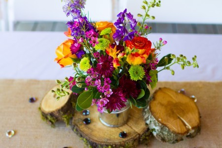 Centerpiece of Flowers in a watering can on rounds of wood