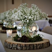 Babysbreath flowers in a fishbowl vase surrounded by pinecones on a round of wood.