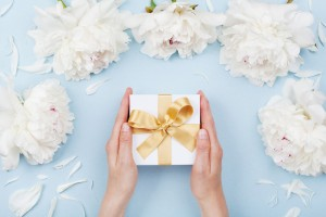 Hands holding a gift in a white box with a gold bow, surrounded by white flowers.