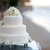 Three-tiered wedding cake with flowers on top.